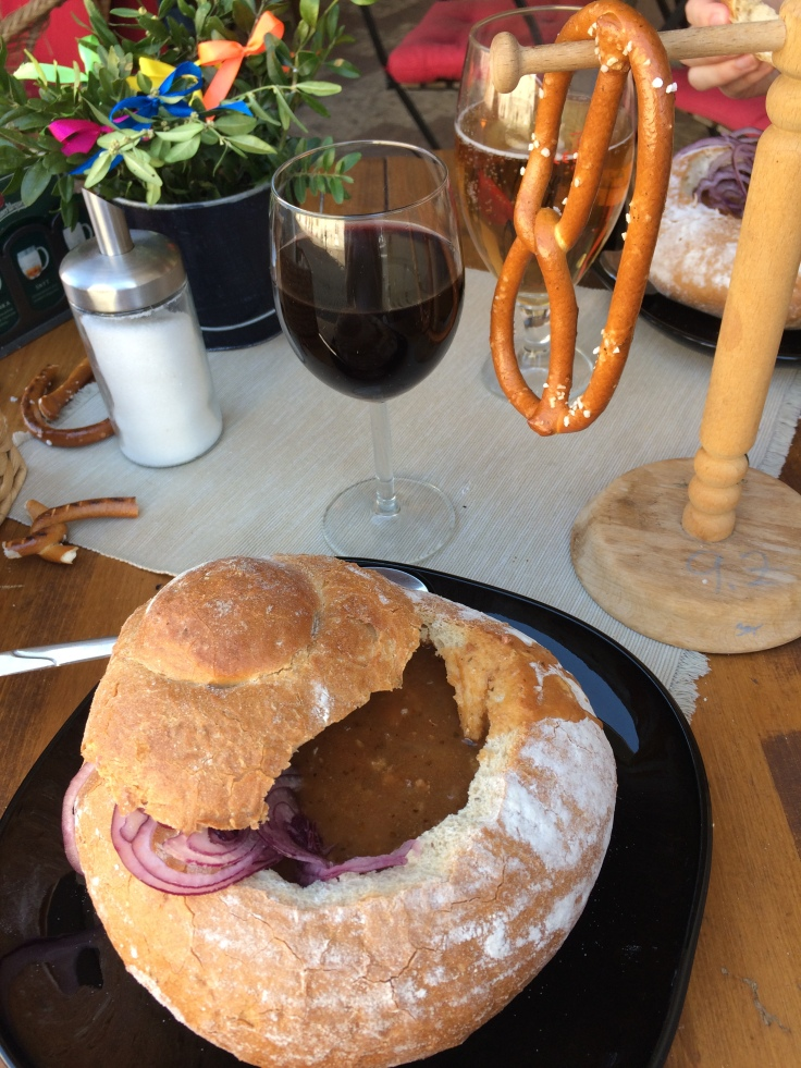 Beef goulash soup served in a loaf of bread, with pretzels and a glass of wine